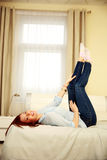 Happy woman lying on the bed with raised legs Stock Photo
