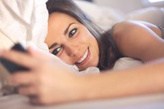 Happy Woman Lying on Bed Reading a Text Message Stock Image