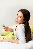 Happy woman lying on bed smiling, reading a text message Royalty Free Stock Images