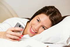 Happy woman lying on bed smiling, reading a text message Royalty Free Stock Photography