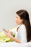 Happy woman lying on bed smiling, reading a text message Royalty Free Stock Photo