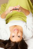 Happy woman lying on bed smiling, reading a text message Stock Image