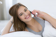 Happy woman lying on the bed Stock Images