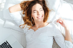 Happy woman lying on the bed and waking up Stock Image