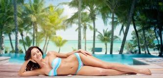 Happy woman lying in bikini swimsuit on beach Stock Images