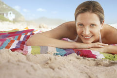 Happy Woman Lying On Blanket At Beach Royalty Free Stock Photography