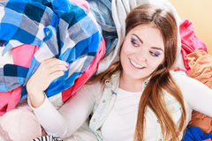 Happy woman lying on clothes. Mess and disorder. Stock Photos