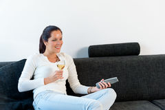 Happy woman lying down couch watching TV Royalty Free Stock Photo
