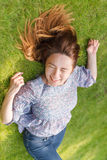 Happy woman lying down on green grass Royalty Free Stock Photo