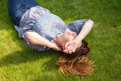 Happy woman lying down on green grass Stock Photo
