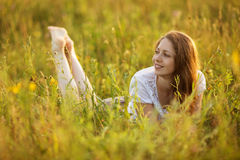 Happy woman lying in a field of grass and flowers Stock Photography