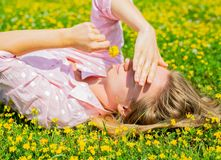 Happy woman lying on the field in grass with yellow flowers outdoors. Enjoy nature. Allergy free. Beautiful girl is relaxing lying on the grass in the meadow stock photo