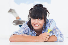 Happy woman lying on floor holding paint brush Stock Image