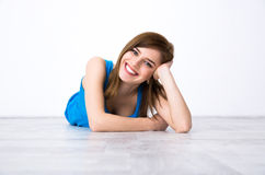 Happy woman lying on the floor. Portrait of a beautiful happy woman lying on the floor Royalty Free Stock Images