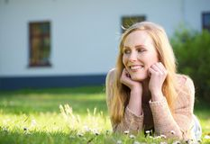 Happy woman lying on grass outdoors and smiling Stock Photo