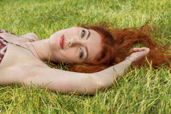 Happy Woman Lying on Grassy Ground Stock Photo