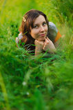 Happy woman lying in green grass Royalty Free Stock Image