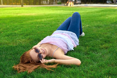 Happy woman lying on a green lawn Stock Photo