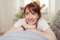 Happy Woman Lying on her Stomach on the Couch Stock Images