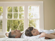 Happy Woman Lying With Husband In Bed Royalty Free Stock Image