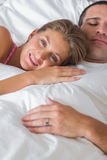 Happy woman lying on husbands chest in bed. Happy women lying on husbands chest in bed smiling at camera at home in bedroom Royalty Free Stock Photos