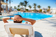 Happy woman lying on a lounger by the pool at the hotel Stock Photos