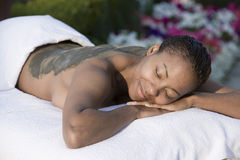Happy Woman Lying On Massage Bed With Mud Pack Applied On Back Royalty Free Stock Photography