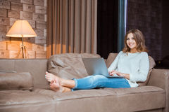Happy woman lying on the sofa with laptop computer Stock Images