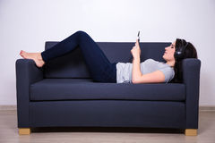 Happy woman lying on sofa and listening music with mobile phone Royalty Free Stock Image