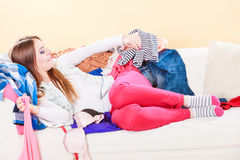 Happy woman lying on sofa in messy room at home. Stock Photo