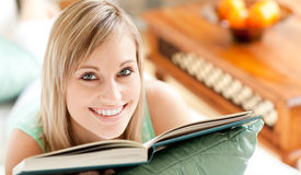 Happy woman lying on a sofa reading a book Royalty Free Stock Photography
