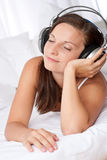 Happy woman lying on white sofa listening to music Stock Photo