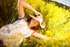 Happy woman lying among yellow wildflowers Royalty Free Stock Image