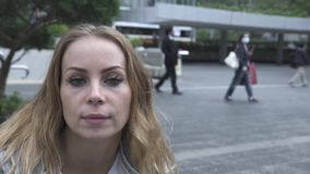 Happy woman on m moderncity street background looking to camera. Face pretty woman with freckles smiling and posing from. Camera on urban street in big city stock video footage