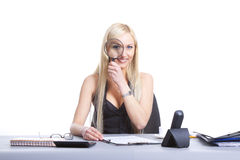 Happy woman magnifying. Happy woman sitting at office desk, smiling. Isolated on white background stock photo