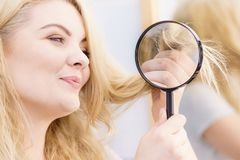 Happy woman looking through magnifer at hair stock photography