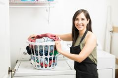 Portrait of smiling woman holding laundry basket. Happy woman maid in the laundry room near the washing machine with dirty clothes Stock Images