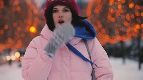 Happy woman make air blow kiss walking along winter alley. Happy woman make air blow kiss at camera walking along winter alley where trees decorated by garlands stock footage