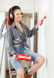 Happy  woman makes repairs in the apartment Royalty Free Stock Photo
