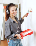 Happy  woman makes repairs in the apartment Stock Photos