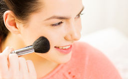 Happy woman with makeup brush blushing cheekbone Royalty Free Stock Image