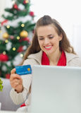 Happy woman making Christmas shopping on internet Royalty Free Stock Images