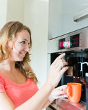 Happy  woman making coffee cup machine Stock Image