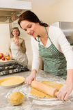 Happy woman making dough for apple pie Stock Image
