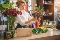 Happy woman making flower masterpiece Stock Photography