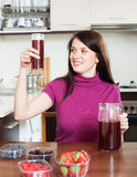 Happy woman making fresh beverages with berries Stock Photography