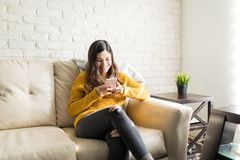 Happy Woman Making Friends On Internet. Relaxed young woman using messaging application on smartphone at home stock photos