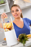 Happy woman making fruit juice Royalty Free Stock Photos