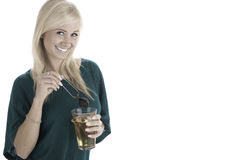 Happy woman making a glass of tea. Happy woman just made a tall glass of tea, removing the strainer royalty free stock photos