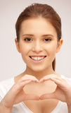 Happy woman making heart gesture Stock Photos